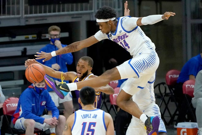 DePaul's Nick Ongenda (14) pressures Western Illinois' Justin Brookens under the basket during the first half of an NCAA college basketball game Wednesday, Dec. 23, 2020, in Chicago. [AP Photo/Charles Rex Arbogast]