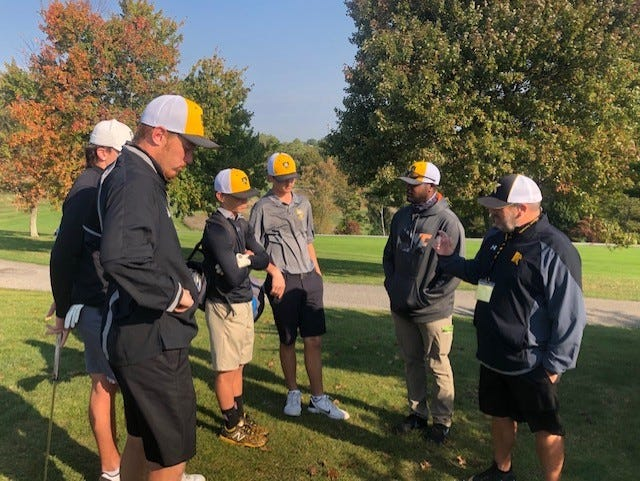 Coaches Josh Blowe and Bill Ack provide instructions to their team at the state golf championships in Wheeling.