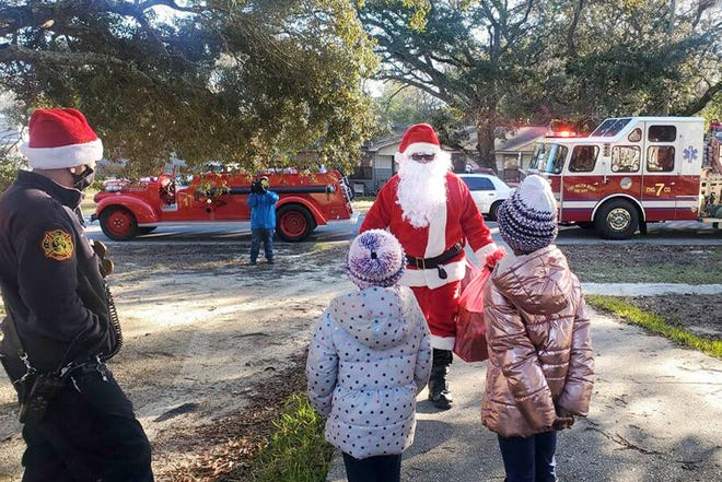 Dressed as Santa Claus, a Fort Walton Beach firefighter delivers toys to children Christmas morning.