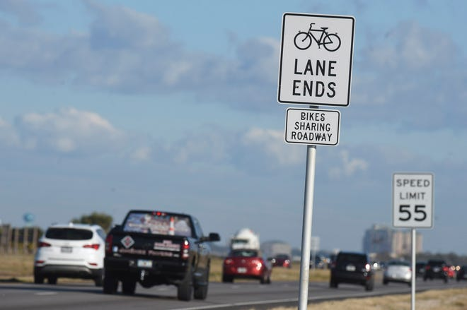 Eastbound motorists traveling U.S. Highway 98 on Okaloosa Island Tuesday pass signs that say share the road with bicyclists. Okaloosa County plans to build a 12-foot-wide pedestrian and bicycle path along the south side of U.S. Highway 98 on Okaloosa Island that would run from Pier Road east to the Marler Bridge.