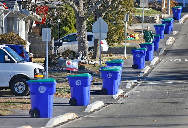 Trash cans are lined up along Taunton Avenue in Rockland for curbside pickup.