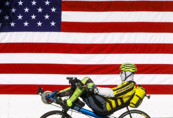 A cyclist wearing a protective mask pedals a recumbent road bike past a giant flag on the side of Le Bar vin Palm Beach on April 1, 2020. [Damon Higgins/palmbeachdailynews.com]