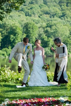 """A couple """"breaks the glass"""" after being wed by celebrant Lois Heckman."""