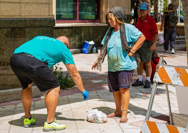 Harry Stern, from The Lord's Place, puts a bag of food on the ground for a homeless woman beside the Mandel Public Library in downtown West Palm Beach on March 31, 2020.