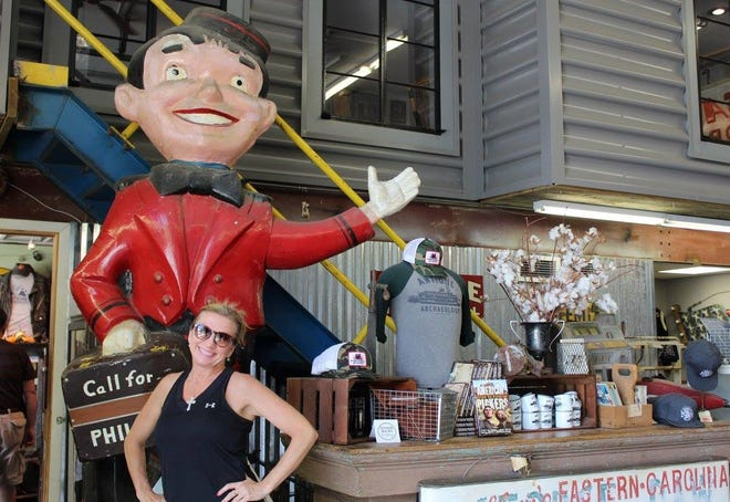 The Social Butterfly Kristi K. Higgins poses for a photo standing in front of the famous Philip Morris cigarette bellhop at the Home of the American Pickers in Le Claire, Iowa in October of 2017.