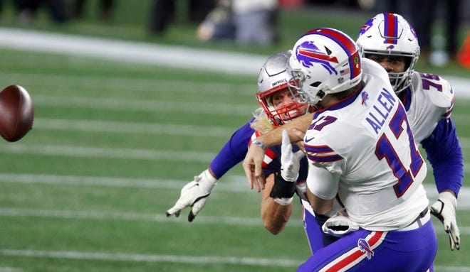 Patriot defensive lineman Chase Winovich puts pressure on Buffalo quarterback Josh Allen, forcing him to get rid of the ball in the first half Monday night.