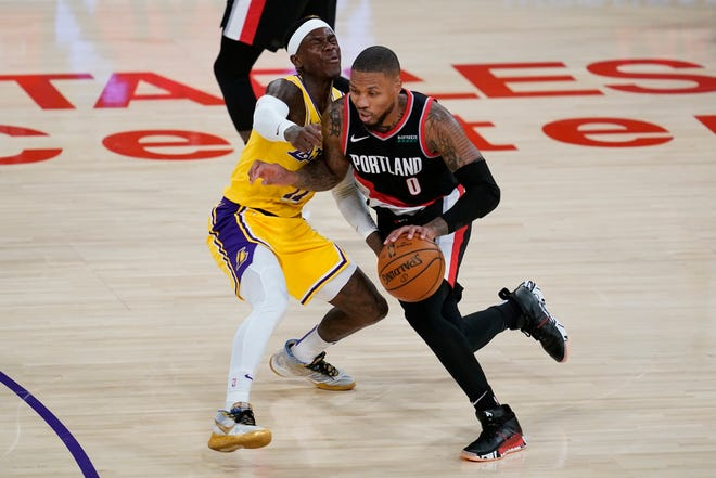 Portland's Damian Lillard, who had 31 points, drives on Los Angeles Lakers guard Dennis Schroeder during the second quarter of the Trail Blazers' 115-107 win over the Lakers on Monday in Los Angeles.