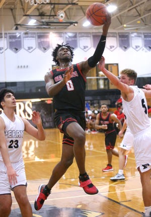 Kobe Johnson of McKinley (0) drives through the lane while being guarded by Haytham Hmeidan (23) and Jared Pettay (5) of Perry during their game at Perry on Monday, Dec. 28, 2020.