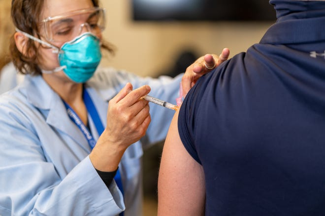 A Canton firefighter receives the COVID vaccine from a Canton Public Health worker.