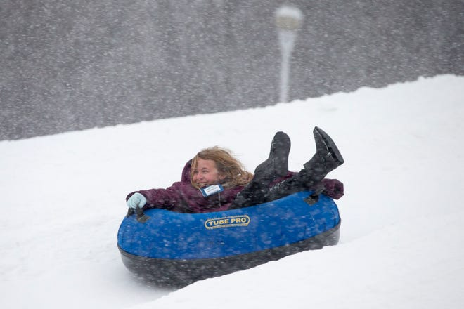 Emalie Fowler, 8, of Floral City, Florida, tubes down the hill while experiencing snow for the first time in her life on opening day at Snow Park at Alpine Hills on Tuesday in Rockford.