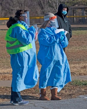 Health care workers clothed in personal protective equipment distribute information at a free COVID-19 test collection sponsored by Salina Family Healthcare Center last year. Salina Family Healthcare Center will be hosting a free COVID-19 community testing event in coordination with Salina's Salvation Army, NAACP and North Salina Community Development on Saturday, Jan. 23, at the Salvation Army, 1137 N. Santa Fe Ave. in Salina. (SALINA JOURNAL FILE PHOTO)