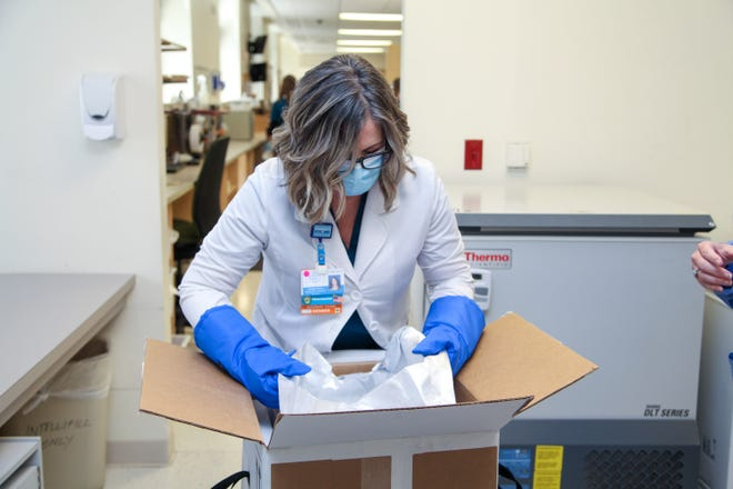 Pharmacist Carolyn Piazza begins unloading the first doses of COVID-19 vaccines at Flagler Hospital in St. Augustine.