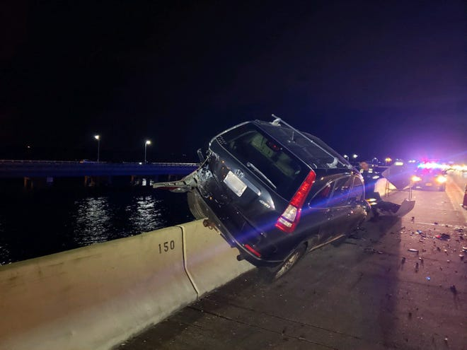 A Honda SUV hangs on the side of the southbound lanes of the Sunshine Skyway bridge on Dec. 28, 2020, after a crash.