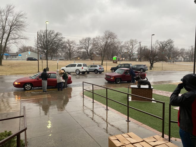 Highland Park High School faculty and staff carry boxes of food out to cars that have arrived for a food distribution event.