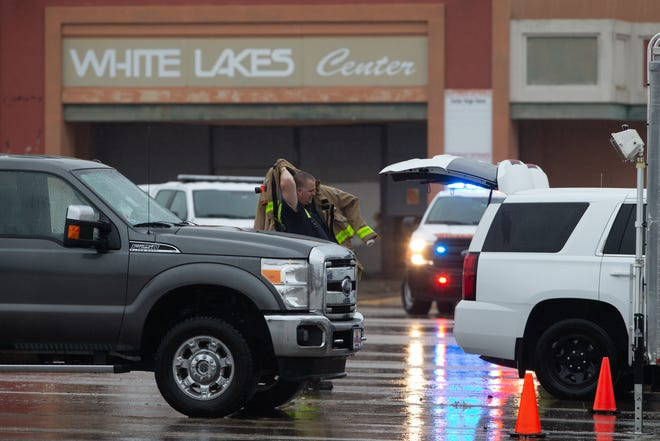 A Topeka firefighter dons his jacket outside the east entrance to the former White Lakes Mall at 3600 S.W. Topeka Blvd. on Tuesday afternoon. A fire broke out inside the building early Tuesday.