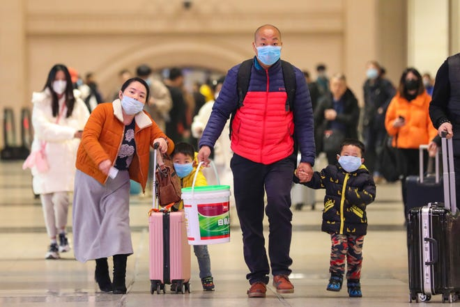 In this  Jan. 21 photo, travelers wearing face masks walk with their luggage at Hankou Railway Station in Wuhan in southern China's Hubei province.