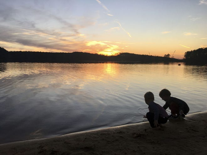 """This image provided by Lucy O'Donoghue shows children playing by a lake. Although this year's quarantine limited Lucy O'Donoghue's opportunities for travel, she found ways to focus on her two sons by taking them for """"microholidays"""" at a beach near their Georgia home."""