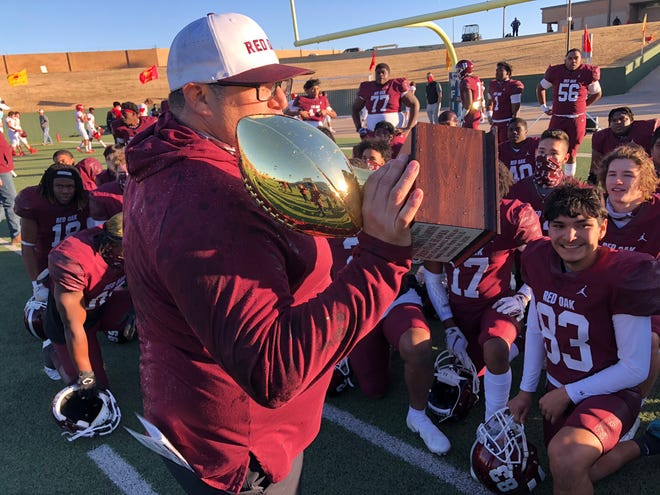 Red Oak head football coach Michael Quintero holds the region semifinal trophy as he talks to his players following Saturday's 42-41 double-overtime victory over Lubbock Coronado in Wichita Falls. The Hawks rallied from a 28-7 third-quarter deficit and will play Mansfield Summit in a season rematch at 11 a.m. on New Year's Day at Globe Life Park in Arlington.