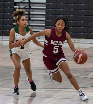 Red Oak's Breanna Davis (5) drives past Waxahachie's Taz Valencia during their matchup last December at Mike Turner Gymnasium. Davis scored 26 points in Thursday night's 54-48 region quarterfinal playoff victory over Highland Park.