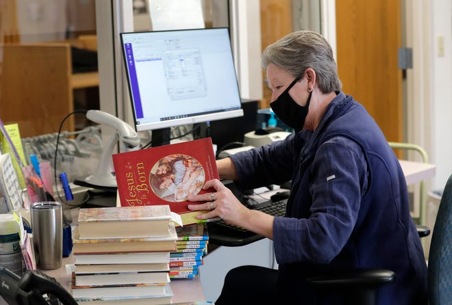 Librarian assistant Jane Werner changes labels on children's books as part of the genrefication of the collection at the Little Chute Public Library.
