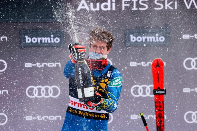 United States' Ryan Cochran-Siegle celebrates on the podium after winning an alpine ski, men's World Cup Super G, in Bormio, Italy, Tuesday, Dec. 29, 2020.