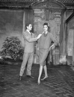 Dalam file foto 13 September 1960 ini, desainer Paris Pierre Cardin, dengan salah satu modelnya, menunjukkan seragam baru yang dia buat untuk pembawa acara televisi Prancis di Paris.