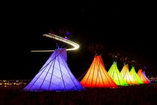 Teepees are lit with colored lights in this long exposure photograph as a Delta flight from Minneapolis flies overhead as it approaches Billings Logan International Airport at Swords Park in Billings, Montana, on Dec. 19, 2020. The installation is in honor of those who have died this year and also a symbol of hope. (Mike Clark/Billings Gazette via AP)