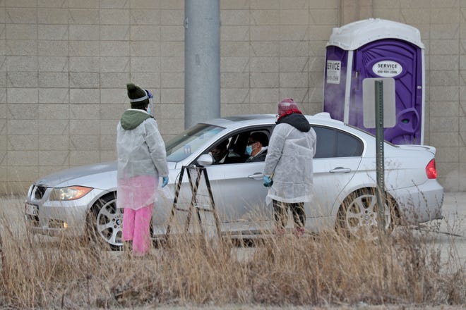 A driver is tested for COVID-19 at a mobile testing unit at Barack Obama School in Milwaukee on Tuesday.