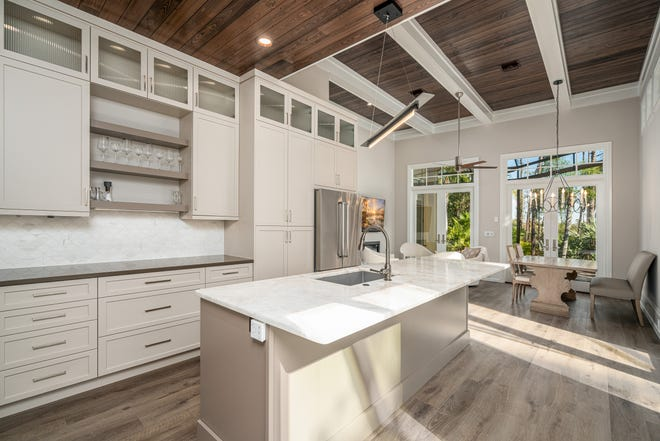 The remodel by Green Mountain Builders of a home in Pelican Landing included an open kitchen with contemporary cabinetry, an expansive island and a wood ceiling and decorative beams.