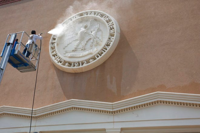 A worker power-washes the New Mexico state seal at the Capitol in Santa Fe, Aug. 24, 2020.