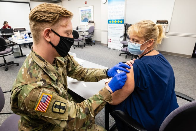 U.S. Army National Guard Sgt. Christian Grow, left, administers a COVID-19 vaccine to Lake Huron Medical Center registered nurse Brenda McCracken during a clinic at Lake Huron Medical Center Tuesday, Dec. 29, 2020.
