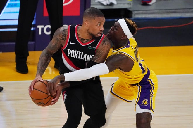 Portland Trail Blazers guard Damian Lillard (0) is defended by Los Angeles Lakers guard Dennis Schroder (17) in the fourth quarter at Staples Center. The Trail Blazers defeated the Lakers 115-107.