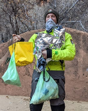 """""""Ranger John"""" holding trash and human waste found on the Narrows trail in Zion National Park."""