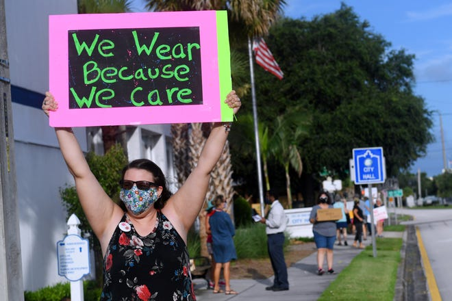 Lindsay Lacy, of Sebastian, shows her support of wearing face masks on Tuesday, July 21, 2020, in front of the City Hall in Vero Beach. The council held discussions on whether to draft a mandate, but with two councilmen - Joe Graves and Robbie Brackett - opposed to a mandate, the council opted against moving forward with drafting a proposed ordinance.