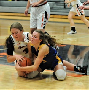 Ridgewood's Kelley Masloski (white) and West Muskingum's Madalynn Kennedy (blue) fight for a loose ball during Monday's game at Ridgewood. The Tornadoes won 46-38.