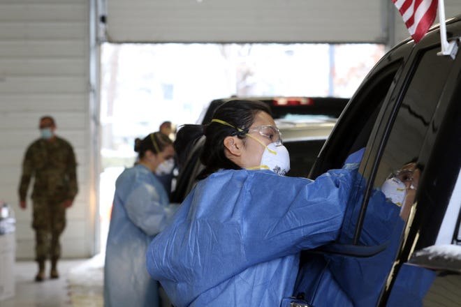 Yen Nguyen, a medic with the Ohio Army National Guard, administers a COVID-19 test during a drive-thru testing event at the Muskingum County Fairgrounds in December.