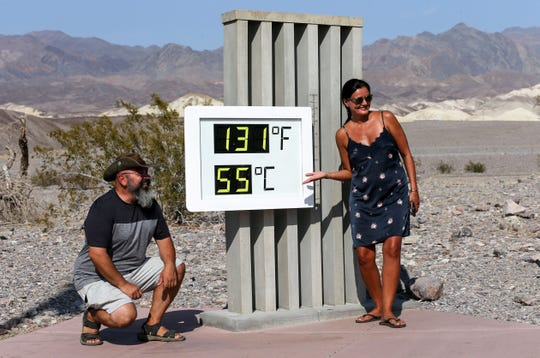 Visitors gather for a photo in front of an unofficial thermometer at Furnace Creek Visitor Center on August 17, 2020, in Death Valley National Park, California. The temperature reached 130 degrees at Death Valley National Park on August 16, hitting what may be the hottest temperature recorded on Earth since at least 1913, according to the National Weather Service.
