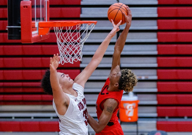 Weiss post Cameron Jackson, left, tries to block a dunk attempt by Manor's Carl Chester during the fourth period at the District 18-5A boys basketball game on Dec. 29 at Weiss High School. Manor cruised to a 70-49 win.
