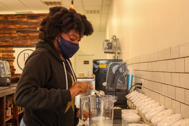 Sarah Stokes, 13, pours protein powder into the blender at Pflugerville Nutrition.