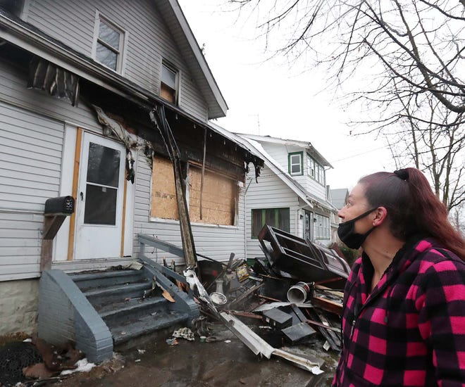 Kimberly DeWitt looks up Wednesday at the window where she escaped a Christmas Day fire in Akron. Two family dogs died in the blaze.