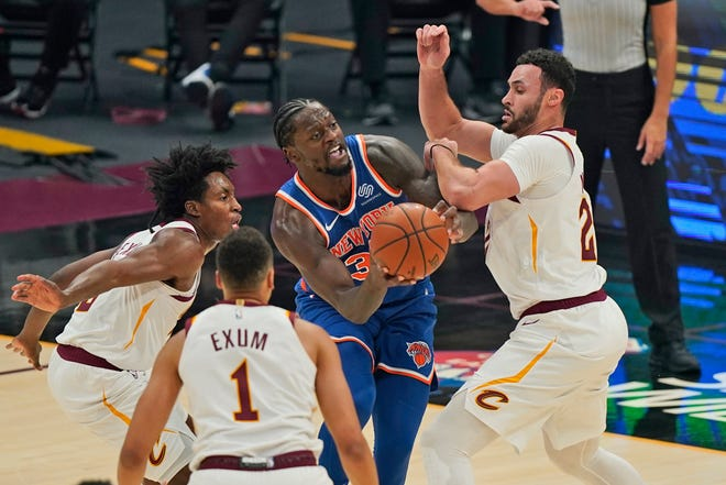 New York Knicks forward Julius Randle, center, tries to get past Cavaliers guard Collin Sexton, left, forward Larry Nance Jr., right, and guard Dante Exum during the Knicks' 95-85 win Tuesday night in Cleveland. [Tony Dejak/Associated Press]