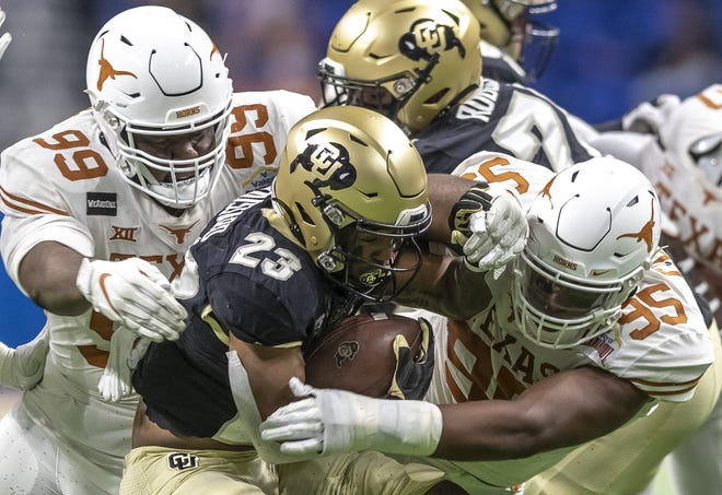 Texas defensive linemen Keondre Coburn, left, and Alfred Collins tackle Colorado running back Jarek Broussard during the first quarter of Tuesday's 55-23 Alamo Bowl win.