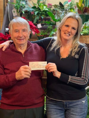 Angie Heimberger of Four Seasons Flowers and Gifts in Loudonville presents Gene Heimberger of Helping Hand Services, a group that helps those in need in Loudonville, with a check for $693. Money was raised through a raffle conducted at Four Seasons for a Grapevine Christmas Tree. This marks the 15th year that Heimberger has held the grapevine tree raffle for Helping Hand.