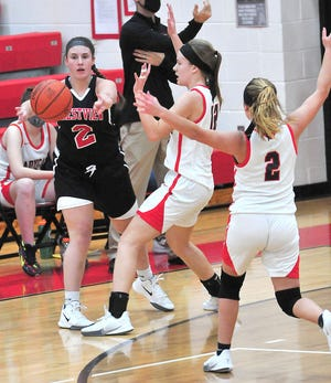 Crestview's Lindsey Them (2) throws a pass around the defense of New London's Emilee Rowland (12) and Jocelyn Speicher (2) during girls basketball action Tuesday at New London High School. The Cougars won, 51-24.