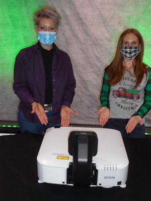 Sally Hollenbach (left), director of The Ohio Theatre, and Marissa Burd, president of the Loudonville Theatre & Arts Committee, unveil the new Epson Ultra Short-Throw Projector, the newest piece of equipment purchased through grants received to support the continued development of the Ohio Theatre, the centerpiece for entertainment and arts education in Loudonville.