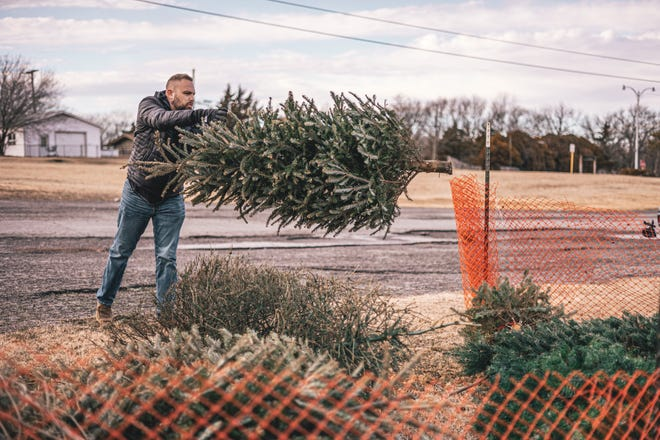 Caleb Gordon takes advantage of the free Christmas tree mulching drop-off at the upper-level parking lot at Sooner Park in Bartlesville. Trees will be accepted at the site until Jan. 24.