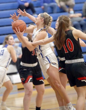 Boonville junior Addi Brownfield (14) drives to the basket and puts up a shot between two Tipton defenders in the second half Tuesday night at the Windsor gymnasium at Boonville High School. Boonville won the game against Tipton 57-41.