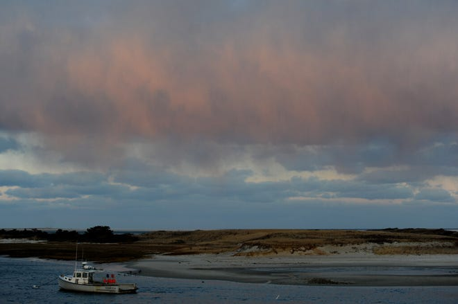 The last bit of sun reaches the clouds above Tern Island in Chatham.