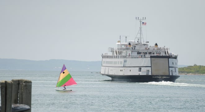 A sunfish boater sails past the Steamship Authority's M/V Martha's Vineyard ferry on its way from Woods Hole to Martha's Vineyard.