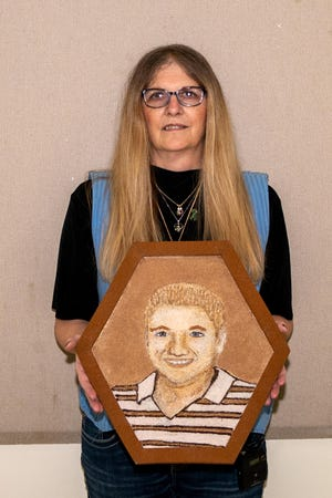 Carmela Wiant holds the floragraph of her son.